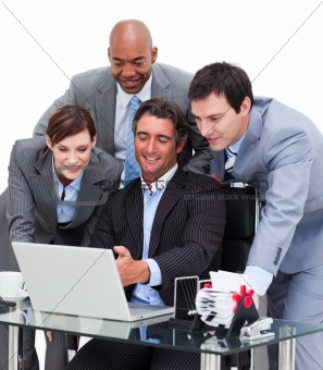 Multi-cultural business team working at a computer