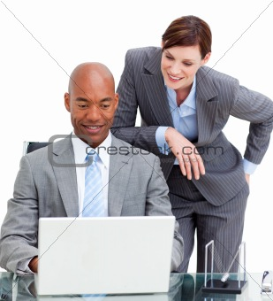 Brunette manager assisting her colleague at a computer