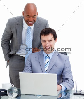 Ethnic manager assisting his colleague at a computer