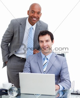 Smiling manager assisting his colleague at a computer