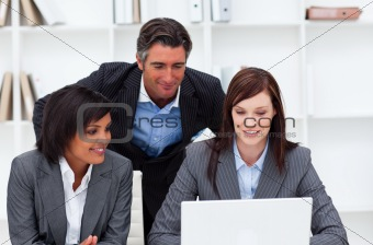 Charming businesswomen and their colleague working at a laptop