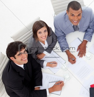 Three colleagues smiling at the camera in a meeting