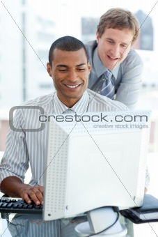 Positive businessman working at a computer in the office