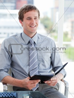 Charming male executive looking at his agenda