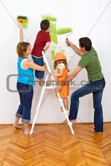 Happy family redecorating the house - painting