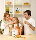 Happy healthy family drinking orange juice