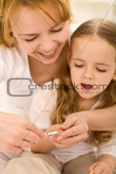 Grooming theme - woman cuts little girls nails