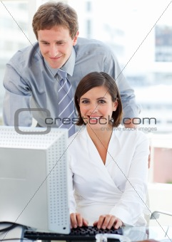Attractive businesswoman working at a computer with her manager