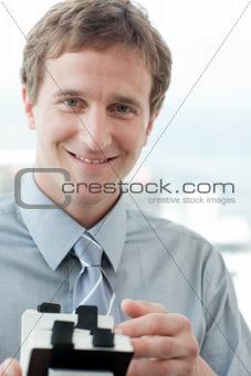Smiling businessman holding a business card holder