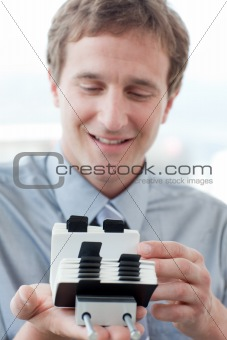 Caucasian businessman consulting a business card holder