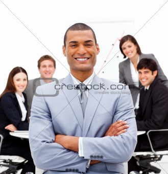 Smiling male executive with folded arms sitting in front of his