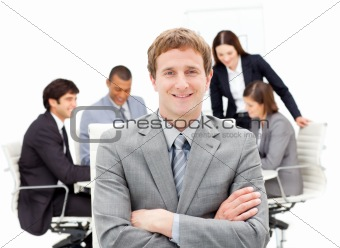 Assertive male executive with folded arms sitting in front of hi