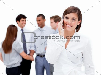 Attractive businesswoman on phone in front of her team