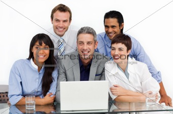 Smiling business group using a laptop