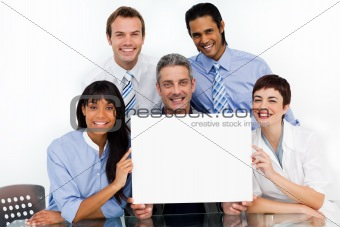 A business group showing diversity holding a white card 