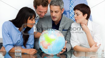 International business people looking at a terrestrial globe