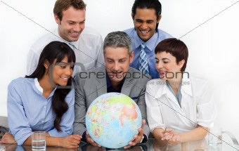 Smiling business people looking at a terrestrial globe