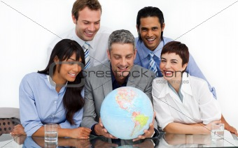 A business group showing diversity looking at a terrestrial glob