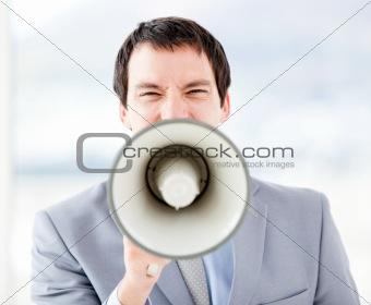Portrait of an stressed businessman using a megaphone