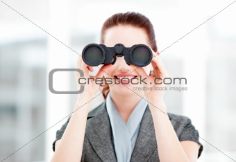 Attractive businesswoman using binoculars