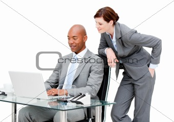 Confident business partners working at a computer in the off