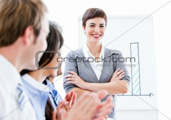 Portrait of a smiling businesswoman talking at her colleague dur