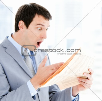 Portrait of a exited businessman reading a newspaper
