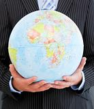 Close-up of a charismatic businessman holding a globe