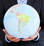 Close-up of a relaxed businessman holding a globe