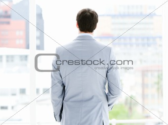 Ambitious businessman looking through a window