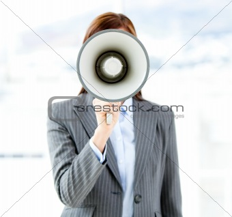 Portrait of an confident businesswoman using a megaphone