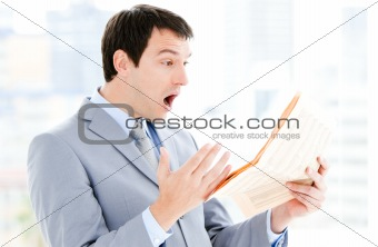 Portrait of a annoyed businessman reading a newspaper