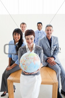 Positive international business people holding a terrestrial glo