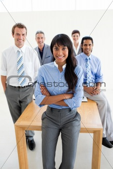 Assertive manager with folded arms in front of her team
