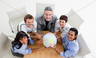 Smiling business people holding a globe