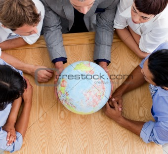 close-up of business people looking at a globe
