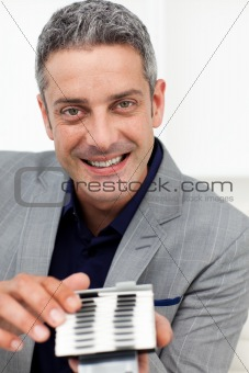 Smiling businessman holding a business card holder