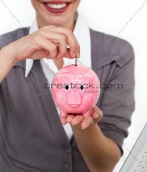 Close-up of a businesswoman saving money in a piggybank