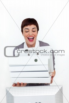 Radiant businesswoman putting a pile of folders on a desk