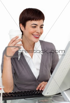 Female executive drinking a coffee at her desk