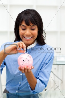 Enthusiastic ethnic businesswoman saving money in a piggybank