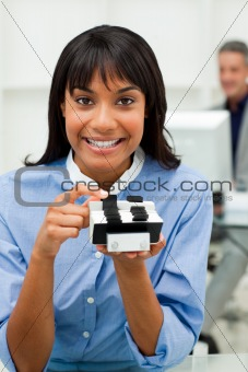 Self-assured businesswoman holding a business card holder