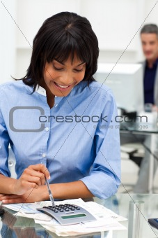 Smiling businesswoman using a calculator