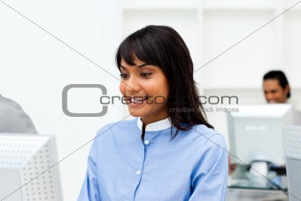 Charming ethnic businesswoman working at a computer