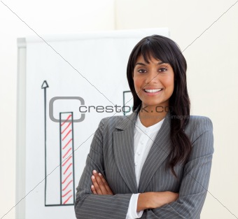 Afro-american businesswoman with folded arms in front of a board