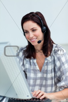 Charming businesswoman with headset on working at a computer