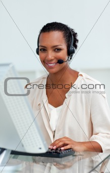Afro-american businesswoman with headset on working at a compute
