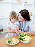 Dissatisfied blond girl eating vegetables with her mother