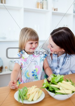 Attentive mother and her daughter eating vegetables