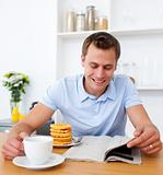 Cheerful man reading a newspaper while having breakfast